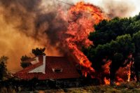 A house is threatened by a huge blaze during a wildfire in Kineta, near Athens, on July 23, 2018.CreditValerie Gache/Agence France-Presse — Getty Images