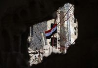 The Syrian national flag flies amid war damage in the city of Daraa's al-Balad district on July 12, 2018. (Mohamad Abazeed/AFP/Getty Images)