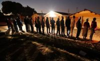 Zimbabwean voters line up before dawn Monday to cast their ballots in the country's general elections in Harare. (Reuters)