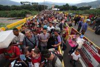 Venezolanos cruzan la frontera entre su país y Colombia, separados por el puente Simón Bolívar sobre el río Táchira. Credit George Castellanos/Agence France-Presse — Getty Images
