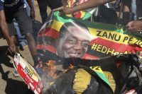 Opposition supporters burn posters of Zimbabwean President Emmerson Mnangagwa while protesting election results in Harare on Aug. 1. (AP)