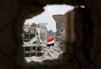 A Syrian flag flying in a rubble strewn street during a flag raising ceremony at the entrance of the Hajar al-Aswad neighborhood on the southern outskirts of the capital Damascus in May, after the regime seized the area earlier in the week from the Islamic State.CreditCreditLouai Beshara/Agence France-Presse — Getty Images