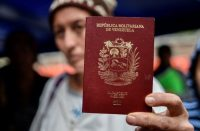 Una mujer venezolana muestra su pasaporte frente a una oficina migratoria colombiana el 20 de agosto de 2018. Credit Luis Robayo/Agence France-Presse — Getty Images