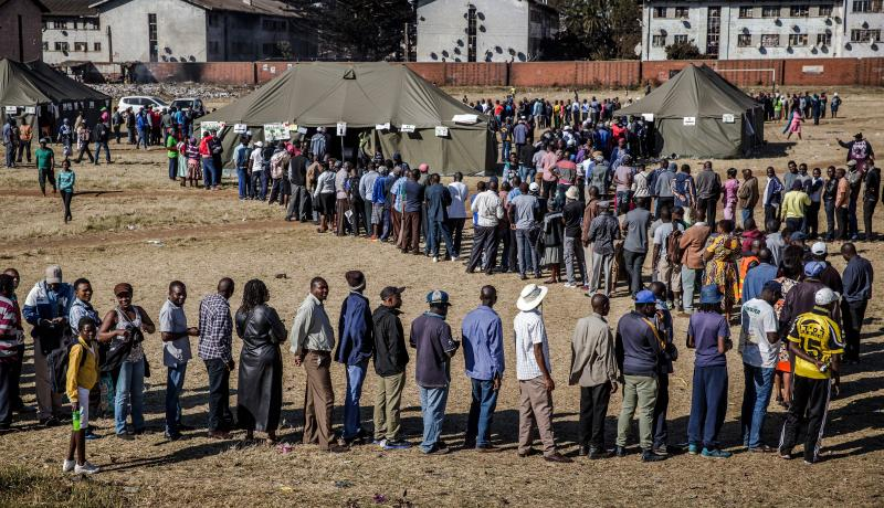 People queue in order to cast their ballot outside a polling station located in the suburb of Mbare in Zimbabwe's capital Harare, on 30 July 2018. Photo: Luis Tato/AFP/Getty Images.