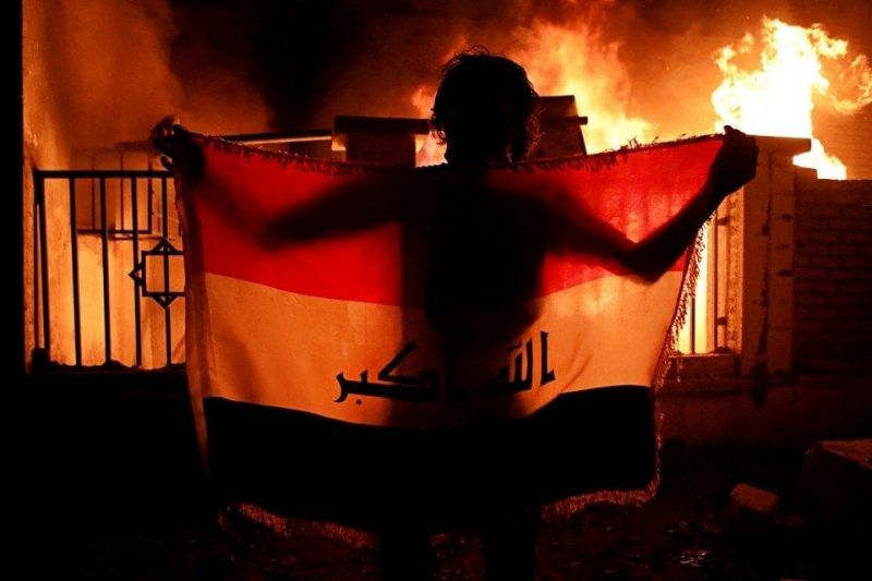 A man holds a national flag while protesters burn the municipal complex during protests demanding better public services and jobs in Basra, 340 miles southeast of Baghdad, Wednesday, Sept. 5, 2018. (AP Photo/Nabil al-Jurani)