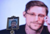 """US former CIA employee and whistle-blower Edward Snowden, delivers a speech by video conference during the debate at the """"Estoril Conferences - Global Challenges Local Answers"""" held at Estoril, outskirts of Lisbon, on May 30, 2017. The event will be running from May 29 until June 1. / AFP PHOTO / PATRICIA DE MELO MOREIRA (Photo credit should read PATRICIA DE MELO MOREIRA/AFP/Getty Images)"""