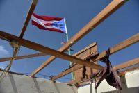 El 28 de septiembre de 2017, una bandera de Puerto Rico ondea sobre una casa dañada por el huracán en Yabucoa, al este de la isla. Credit Héctor Retamal/Agence France-Presse — Getty Images