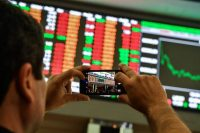 A visitor took pictures of an electronic board at the São Paulo Stock Exchange in São Paulo, Brazil, on Wednesday.CreditCreditNelson Almeida/Agence France-Presse — Getty Images