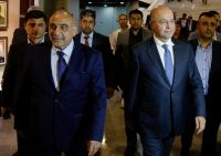 Iraq's new president, Barham Salih, front right, walks with the new prime minister, Adel Abdul Mahdi, front left, in the parliament building in Baghdad on Oct. 2. (Karim Kadim/AP)