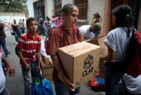 En mayo de 2018, una mujer carga una caja de productos de alimentación básica que el gobierno venezolano oficializó en 2016. créditoAriana Cubillos/Associated Press