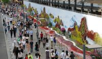 People walk past the 'Belt and Road' ecological wall in Beijing during the Belt and Road Forum for International Cooperation in May. Photo: Getty Images.