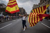 Una mujer ondea las banderas de España y Cataluña durante la celebración del Día de la Hispanidad en 2017 en Barcelona. Credit Santi Palacios/Associated Press