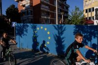 Children ride bicycles next to a wall painted with the European Union flag last month in the southern Serbian town of Presevo. (Armend Nimani/AFP/Getty Images)