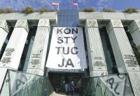 "People enter the Supreme Court in Warsaw on Oct. 11 under a banner reading ""Constitution."" (Alik Keplicz/AP)"