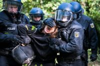 Police officers with a protester seeking to block coal mining in the Hambach Forest near Cologne, Germany.CreditCreditJana Bauch/Agence France-Presse — Getty Images