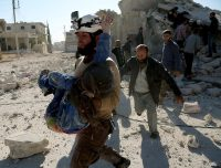 ALEPPO, SYRIA - NOVEMBER 6: Syrian civil defense team member carries a wounded girl after warcrafts belonging to Russian army carried out airstrikes over Urum al-Kubra region in Aleppo, Syria on November 6, 2016. (Photo by Beha el Halebi/Anadolu Agency/Getty Images)