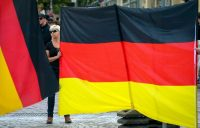 A right-wing protester held a German flag during a protest in Koethen, Germany, in September.CreditCreditSrdjan Suki/Epa-Efe, via Rex