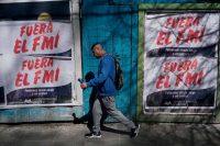 En septiembre de 2018, un hombre pasa por carteles en contra de las negociaciones de Argentina con el Fondo Monetario Internacional. Credit Eitan Abramovich/Agence France-Presse — Getty Images