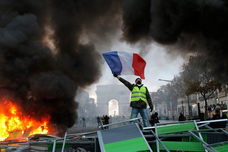 A member of the Gilets Jaunes, or Yellow Vests movement, at a protest against rising fuel taxes, on the Champs-Élysées in Paris on Saturday. Credit Michel Euler / Associated Press