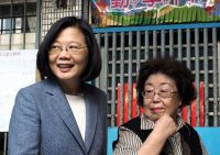 Taiwanese President Tsai Ing-wen, left, waits to vote in Taipei on Saturday. (David Chang/EPA-EFE)