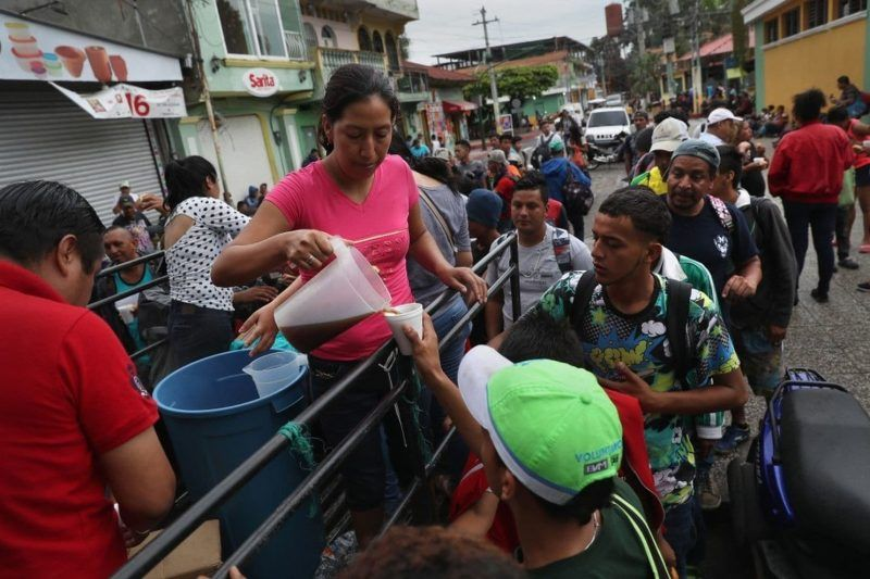 Volunteers serve coffee to members of an immigrant caravan — mostly from Honduras — as they prepare to cross the Guatemalan border into Mexico on Oct. 19. (John Moore/GETTY IMAGES)