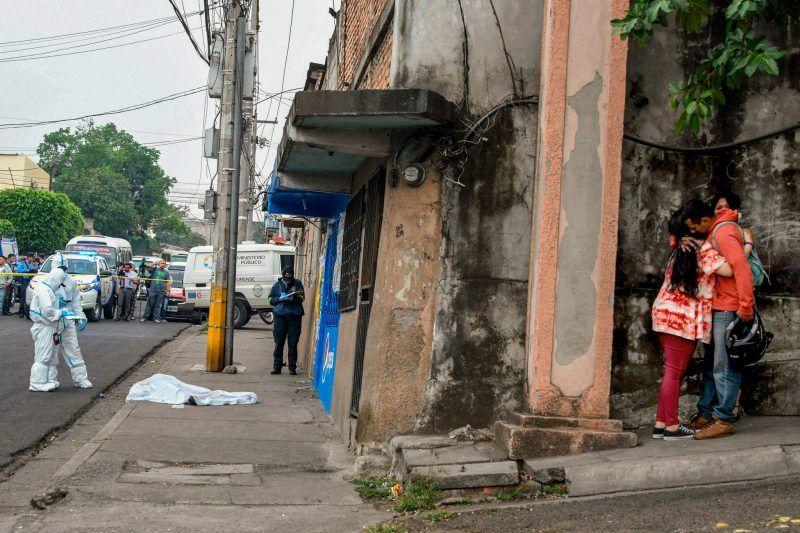 Una hondureña fue asesinada por miembros de una pandilla cuando se dirigía a su escuela. Cerca del cuerpo sin vida de la estudiante, sus familiares se abrazan. Orlando Sierra/Agence France-Presse — Getty Images