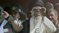 Supreme leader Ayatollah Ali Khamenei looks through binoculars during the test firing of short- and medium-range missiles, on 18 September 2004. AFP PHOTO/Str