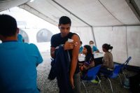 Venezuelan migrants are inoculated against tetanus, influenza, yellow fever, measles and rubella by workers with the Health Ministry and the Red Cross in Tumbes, Peru, on Nov. 1. (Juan Vita/AFP/Getty Images)