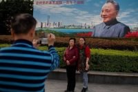 "People pose in front of a billboard featuring China's late paramount leader Deng Xiaoping on the eve of the 40th anniversary of the country's ""reform and opening up"" policy on Monday. (Nicolas Asfouri/AFP/Getty Images)"