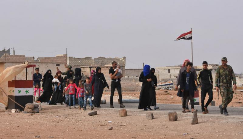 Families walk through the Abu Duhur crossing on the eastern edge of Syria's Idlib province as members of Russian and Syrian forces stand guard. Photo: Getty Images.