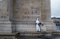 "A worker prepares to clean graffiti reading ""Macron resignation"" on the Arc de Triomphe the day after a French protest of plans to increase the taxes on gasoline and diesel fuel.CreditCreditThibault Camus/Associated Press"