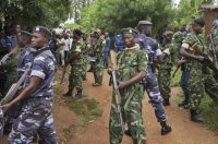 Soldiers and police at the scene where more than 20 people were killed in their homes in an overnight attack in the Ruhagarika community in the rural northwestern province of Cibitoke, Burundi, on May 12, 2018. (AP)