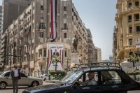 A Cairo intersection with a poster of President Abdel Fattah el-Sisi. The heads of state change in Egypt, but the repressive structures stay the same, Nancy Okail writes.CreditCreditSima Diab/Bloomberg