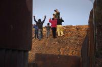 Un grupo de migrantes, miembros de la caravana que aguarda en un refugio en Tijuana, se entregó a un agente fronterizo el 3 de diciembre de 2018, en la frontera entre Tijuana y San Diego. Credit John Moore/Getty Images