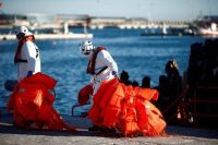 Rescuers carry the life vests of migrants who were intercepted off the Spanish coast. Dec. 10, 2018. (Jon Nazca/Reuters)