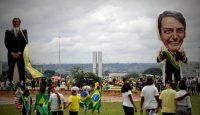 Seguidores del presidente de Brasil, Jair Bolsonaro, caminan frente a un muñeco gigante con su figura en Brasilia (Brasil). Fernando Bizerra Jr. EFE