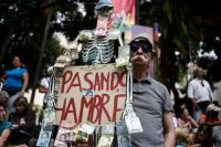 "A Venezuelan opposition supporter holds a placard with the image of human skeleton, Bolivar bills attached to it and a legend reading ""going hungry"" as he waits to listen to self-proclaimed ""acting president"" Juan Guaido on Jan. 25. (FEDERICO PARRA/AFP/Getty Images)"