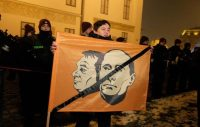 A demonstrator holds a banner with likenesses of Hungarian Prime Minister Viktor Orban and Russian President Vladimir Putin in front of the Hungarian presidental palace in Budapest on Dec. 21 to protest a law about overtime work and pay. (Peter Kohalmi/AFP/Getty Images (Peter Kohalmi/AFP/Getty Images)