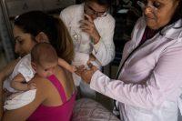 La doctora Rodríguez, a la derecha, y una enfermera, Zoé Alonso Díaz, atienden a una madre y a su hija recién nacida en su casa en La Habana. Credit Lisette Poole para The New York Times