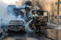 Firefighters put out flames on a burning truck and car during a wave of gang violence in Brazil's northeastern Ceara state, in the city of Fortaleza, on Jan. 3. (Alex Gomes/O Povo/AFP)