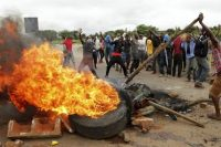 Protesters gather near a burning tire during a demonstration over the hike in fuel prices in Harare, Zimbabwe, on Jan. 15. (AP)