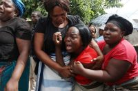 A family member of Kelvin Tinashe Choto reacts during his funeral in Chitungwiza, Zimbabwe, on Saturday. He was killed in a violent crackdown by security forces on protests. (AP Photo/Tsvangirayi Mukwazhi)