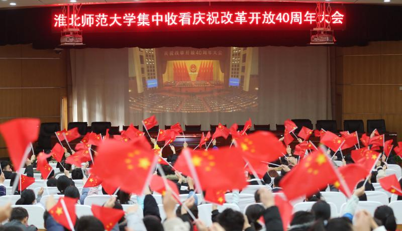 Students holding Chinese national flags watch the live broadcast of the 40th anniversary celebration of China's reform and opening-up at Huaibei Normal University on 18 December. Photo: Getty Images.