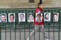 Un hombre pasa por una valla dispuesta frente al Palacio Nacional, en Ciudad de México, con retratos de periodistas asesinados. Credit Yuri Cortez/Agence France-Presse — Getty Images