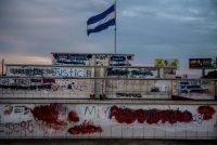 Una bandera de Nicaragua ondea en Managua en diciembre de 2018. En la base se acumulan pintas antigobierno. CreditMeridith Kohut para The New York Times