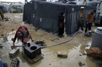 A Syrian family pumps water after heavy rain at a refugee camp in the town of Bar Elias in Lebanon's Bekaa Valley. (Bilal Hussein/AP)