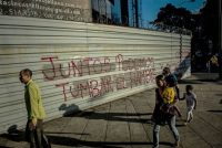 "People in Caracas walk by graffiti that says, in Spanish: ""Together we can take down hunger."" Credit Meridith Kohut for The New York Times"