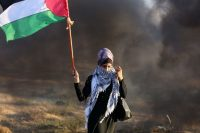 Asmaa, 23, holds up the Palestinian flag at a protest. (Mohammed Zaanoun/Mohammed Zaanoun)