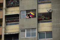 Una mujer ondea la bandera de Venezuela desde una ventana en Caracas, el 12 de marzo de 2019. Credit Ronaldo Schemidt/Agence France-Presse — Getty Images