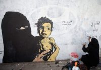 A Yemeni woman writes on a mural about children and women suffering in the time of war in Sanaa, Yemen, in February. (Mohamed al-Sayaghi/Reuters)